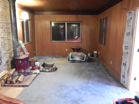 The living room awaits new floors,windows, and wall paint.